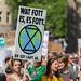 Demonstrantin hält ein Demoschild mit Sanduhr auf der Erde und der Mahnung