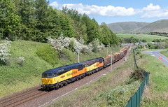 With the Howgills in the background, grids 56049 'Robin of Templecombe 1938-2016' & 56090 sweep south on the WCML at Beckfoot as they take charge of the 6J37 Carlisle to Chick logs on the 22nd May '19. (mark.latham@ymail.com) Tags: 56090 56049 6j37
