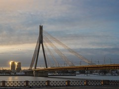Burning Bridge (Wormsmeat) Tags: riga latvia olympus penf 12100mzuikopro bridge river sunlight towerblocks span