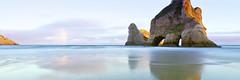 Rainbow and Arched Rock (rubberducky_me) Tags: beach arch southisland newzealand rock rainbow reflection velvia film linhoftechnorama linhof panorama 31