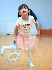 Dance Studio Badminton 15 (ArdieBeaPhotography) Tags: small child girl kid little kindergarten frilly lacy gauzy frothy pink skirt white tshirt teeshirt seatime kitten kitty cat hearts decorated tights long black pigtails hair leggings sstockings smile laugh fun play game foolingaround inside dance studio wood floor artificial light flourescent leap swing strike hit raquet badminton shuttlecock yellow feather empty alone solitarys solo friend enjoy tamronspaf2875mmf28xrdildasphericalif