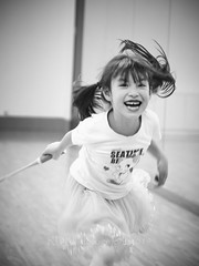 Dance Studio Badminton 02 (ArdieBeaPhotography) Tags: small child girl kid little kindergarten frilly lacy gauzy frothy pink skirt white tshirt teeshirt seatime kitten kitty cat hearts decorated tights long black pigtails hair leggings sstockings smile laugh fun play game foolingaround inside dance studio wood floor artificial light flourescent leap swing strike hit raquet badminton shuttlecock yellow feather empty alone solitarys solo friend enjoy tamronspaf2875mmf28xrdildasphericalif