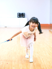 Dance Studio Badminton 06 (ArdieBeaPhotography) Tags: small child girl kid little kindergarten frilly lacy gauzy frothy pink skirt white tshirt teeshirt seatime kitten kitty cat hearts decorated tights long black pigtails hair leggings sstockings smile laugh fun play game foolingaround inside dance studio wood floor artificial light flourescent leap swing strike hit raquet badminton shuttlecock yellow feather empty alone solitarys solo friend enjoy tamronspaf2875mmf28xrdildasphericalif