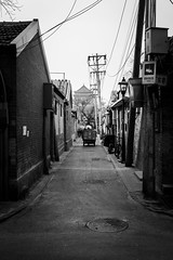 End of the day (Go-tea 郭天) Tags: pékin républiquepopulairedechine narrow alley hutong ancient history historical historic construction architecture bricks lines electric electricity old beijing leaving alone lonely man worker working duty motorbike motorcycle pole cables byke bicycle back backside shadow winter sun sunny street urban city outside outdoor people candid bw bnw black white blackwhite blackandwhite monochrome naturallight natural light asia asian china chinese canon eos 100d 24mm prime movement ride riding rider