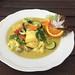 Nahaufnahme zeigt Mittagessen für eine vegane Ernährung, mit Gemüse, Pilzen und Orange in einer Curry Kurkuma Sauce, auf einem weißen Teller