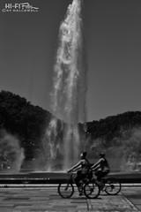 Fountain Riders (Hi-Fi Fotos) Tags: pittsburgh point fountain water spray landmark city urban bikes cycles riders mono bw blackandwhite helios 442 44m manual f2 58mm vintage russian noir nikon d7200 dx hififotos hallewell