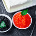 Black and red caviar with butter and spoon on black stone background. Top view