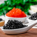 White spoon with black caviar, red and black caviar in bowls behind