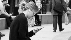 Lost In Music 01 (byronv2) Tags: peoplewatching candid street music earphones phone cellphone mobilephone sitting seated bench bamc park blackandwhite blackwhite bw monochrome saintandrewssquare newtown edinburgh edimbourg scotland woman young blonde