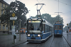 Vor 25 Jahren zeigte sich das Wetter ähnlich regnerisch wie heute. Während eines Platzregens begegnet R1-Wagen 2701, der gleich stadtwärts die erste beschleunigte Fahrt unternehmen wird, am Moosacher Bahnhof dem A-Wagen 256 (Bild: Peter Gimpel) (Frederik Buchleitner) Tags: 256 2701 awagen linie11 linie20 moosach moosachcosimaexpress munich münchen r1wagen strasenbahn streetcar tram trambahn