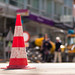 Traffic cone in the foreground and road works in the background