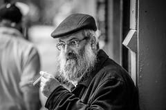 smoke is clarity (Gerrit-Jan Visser) Tags: geimporteerd streetphotography portrait bnw blackandwhite amsterdam beard smoke cigarette cap glasses contact eyes surprised man candid