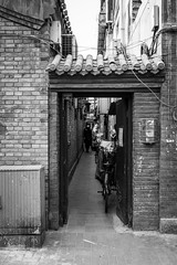 Through the door (Go-tea 郭天) Tags: pékin républiquepopulairedechine hutong ancient old historic history historical alley narrow door opened bricks frame framed lady mask masked bicycles bikes electric cables electricity alone lonely doors cold winter sun sunny shadow protection protected street urban city outside outdoor people candid bw bnw black white blackwhite blackandwhite monochrome naturallight natural light asia asian china chinese canon eos 100d 24mm prime beijing