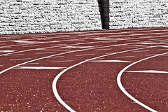 Curves and Lines on a Track (brucetopher) Tags: track race racing trackmeet run running red wall pavement light color minimal sport sports setting line lines shape shapes space spaces curve curves curved lined lining outline shadow
