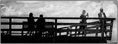 The Pier (Art de Lux) Tags: timmendorf timmendorferstrand deutschland germany ostsee balticsea seebrücke pier menschen personen people frau woman girl geländer railing küste coast panorama sw schwarzweiss bw blackandwhite monochrom monochrome kontrast contrast mft microfourthirds artdelux