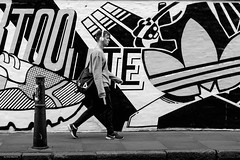 Urban Camouflage (Silver Machine) Tags: london streetphotography street candid graffiti man walking headphones adidas nike trainers advertisement blackwhite bw mono monochrome fujifilm fujifilmxt10 fujinonxf35mmf2rwr
