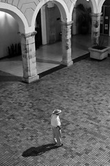 Alone In The Governor's Palace (peterkelly) Tags: digital bw canon 6d northamerica mexico yucatán mérida governorspalace plaza courtyard man hat shadow arch archway gadventures mayandiscovery column pillar