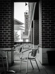 The Café (PEEJ0E) Tags: brick lights white black downtown building architecture umbrella chair table cafe