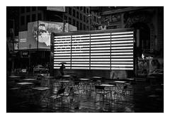 FILM - Stars and Stripes and empty seats (fishyfish_arcade) Tags: 35mm analogphotography bw blackwhite blackandwhite canonsureshotz135 filmphotography filmisnotdead hp5 istillshootfilm monochrome newyork analogcamera compact film ilford mono timessquare rain streetphotography