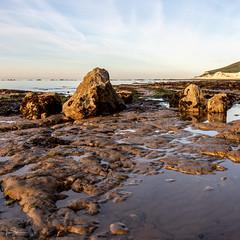 Tides Out at Sunrise (ivanstevensphotography) Tags: sunrise sea beach pebbles sand puddles reflections rocks cliffs grass seaweeds seascape landscape