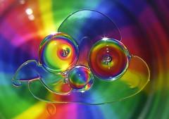 Oil Slick Smile..x HMM! (Lisa@Lethen) Tags: macromondays oilonwater oil water face smile eyes glass coloured card sparkle