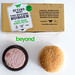 Flatlay of vegan burger patties in the Beyond Meat Burger 10pcs Box, with frozen soy-free and gluten-free patties, next to a burger roll, on white surface