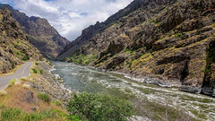 On the border between Oregon and Idaho: The Snake River passes through Hells Canyon, an eerie scene of craggy black volcanic rock. (lhboudreau) Tags: idaho road sky cliff mountain black water grass rock oregon river landscape outdoors rocks outdoor border rocky canyon snakeriver mountainside fissure volcanicrock blackrock lavarock hellscanyon stateborder nf454 hellscanyonscenicbyway hellscanyonroad