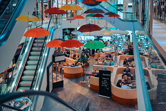 DUESELDORF, GERMANY - OCTOBER 16, 2016: Unidentified individuals enjoy a break in the basement of the Koe gallery. (axel-d-fischer) Tags: grass retail green luxury park historic shopping street landmark fashion walking avenue view rhinewestphalia dusseldorf town pond office travel historical panoramic tree konigsallee stores river perspective architecture boulevard location business kings germany