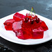 Tasty jelly cubes on white plate with cherry