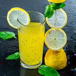 Cold yellow drink with fresh lemon and mint leaves on black background thumbnail