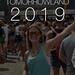 Tomorrowland 2019 Bild zeigt Festivalbesucherin mit Sonnenbrille und Drink vor der Bühne