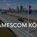 Anfahrt zur Gamescom in Köln wird von Flaggen der Spielemesse begleitet, mit dem Dom im Hintergrund