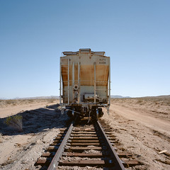 last train to nowhere. mojave desert, ca. 2012. (eyetwist) Tags: eyetwistkevinballuff eyetwist endoftheline railroad tracks mojavedesert california mamiya 6mf 50mm kodak portra 160nc mamiya6mf kodakportra160nc mamiya75mmf35l ishootfilm ishootkodak analog analogue film emulsion mamiya6 square 6x6 mediumformat 120 primes filmexif iconla epsonv750pro filmtagger mojave desert highdesert red sign end rail dead oblivion dirt arid dry aid sleepers crosstie steel stop derail searles lake transport arrow ruin abandoned railway derelict blue sky vanishing point vanishingpoint 6 american west newtopographics railcar hopper