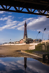 Blackpool Tower and iconic promenade buildings seen from beneath the Central Pier on a sunny evening (sand grown) Tags: blackpooltower blackpoolpromenade promenade pier eveningsun sunshine bluesky