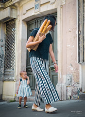 Street - Baguette Mum (François Escriva) Tags: street streetphotography paris france people candid olympus omd photo rue woman colors sidewalk pants dress stripes baguette bread green blue building sign numbre mother daughter baby