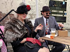 Brighouse 1940s Weekend. Vintage Couple. June 2019 (Simon W. Photography) Tags: brighouse1940sweekend brighouse 1940sweekend 1940s calderdale westyorkshire england wartimeevent wartimeevent2019 vintagefestival victoryrolls hairstyle armedforces nostalgic nostalgia fashion vintage festival retro ww2 1940svintage livinghistory history historic war wwi wwii people person mature groupshot crowd face women couple girls girl woman lady ladies female feminine females candid style sonyrx10iv sonyrx10m4 sonyuk sony sonydscrx10m4 sit sat sitting seated seat reclining relax relaxing