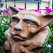 Garden Gargoyle Peaks out of a Planter of Flowers