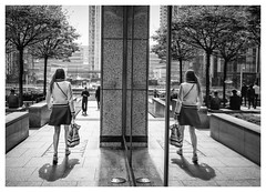 A Little More to the Right (Dave Button) Tags: mono monochrome fuji fujifilm 27mm bw blackwhite street urban city london canarywharf people girl walking reflection mirror border acros cityscape xe2s xe2