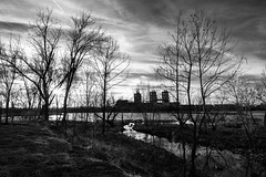 winter trees at sunset (fallsroad) Tags: gatheringplace tulsaoklahoma arkansasriver riversidepark water sky clouds sunset goldenhour blackandwhite bw monochrome powerplant pso tree trees