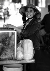 . (Out to Lunch) Tags: ba chieu market saigon ho chi minh city vietnam woman selling food street blackwhite smile happy conical hat jeans jacket bokeh fuji xt1 xf1256r portrait happyplanet asiafavorites