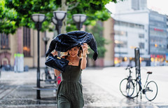 Looking for shelter (graveur8x) Tags: woman candid street portrait rain summer smile girl frankfurt germany deutschland streetphotography strase handbag city urban dof evening running drops regen zeil sonya7iii sony sonyilce7m3 sonyfe85mmf18 85mm f18