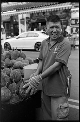The Durian Seller - Chinatown Singapore (waex99) Tags: 2019 400iso bangkok epson kodak leica m6 singapore summitar50mmf2 trix analog film jan v800 man homme chinois chinese summitar vintage 50mm argentique durian fruit stall echoppe marchand street surlevif vif glove gant