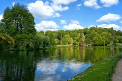 Stourhead Reflections in May. (margaretgeatches) Tags: ripples daisies grass azaleas rhododendrons shrubs trees russett pink yellow green reflections lake shadows sunlight clouds blue sky stourhead wiltshire nationaltrustproperty