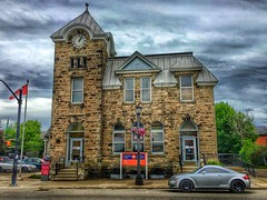 Elora Ontario  -  Canada - Post Office  - 128 Geddes Street - Heritage (Onasill ~ Bill Badzo) Tags: wellingtoncounty elora on ont ontario canada township wellington 128 geddes street heritage po post office mail station centre clock face tower facade rustic stone historic attraction site onasill walking tour village town romanesque style architecture 1911 act thames river sl1 canon eos rebel 18250mm sigma macro lens canadian flag