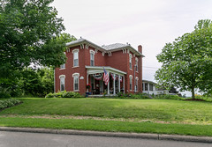 House — Fredericktown, Ohio (Pythaglio) Tags: fredericktown ohio unitedstatesofamerica house dwelling residence historic twostory brick italianate brackets 22windows segmentalarched keystones hoodmolds porch americanflags trees bushes knoxcounty