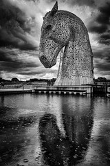 Some people feel the rain. Others just get wet. (michaeljoakes) Tags: horsehead falkirk grangemouth thehelix scotland thekelpies mono monochrome monochromemonday art sculpture rain reflection stormy outdoor horse scottishcanals andyscott forthandclydecanal rivercarron shstructures xf18135mmf3556rlmoiswr fujifilmxt2 visitscotland raindrops stormclouds blackandwhite bnw bw