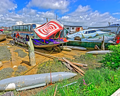 Peculiar Houseboats (Croydon Clicker) Tags: boat barge houseboat mooring jetty torpedo shells riverbank shoreline sand mud weeds sky cloud shoreham sussex westsussex coach bus facade debris
