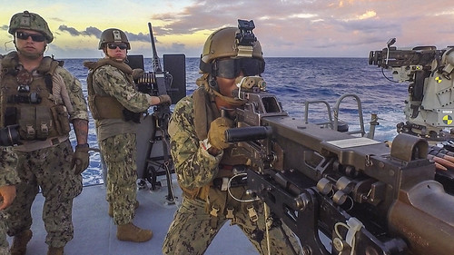 A sailor fires an M2HB 50-caliber machine gun during a live-fire exercise aboard a Mark VI patrol boat