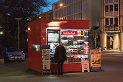ELBERFELD, GERMANY - FEBRUARY 15, 2017: An unidentified male makes some purchases at a red kiosk (axel-d-fischer) Tags: modern retail vividtown elberfeld historic shopping stylish shoppers germany architecture stores richofferings light wuppertalelberfeld downtown