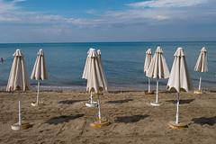 Brollies (Glass Eye Chromatic) Tags: thessaloniki perea greece september 2014 beach parasols umbrellas folded sea shore sand man swimmer swimming panasonic lumix gx7 olympus17mmf18